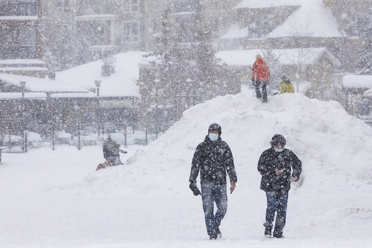 People walk through the snow in the village of Blue Mountain Ski Resort in The Blue Mountains, Ont., on the first day of a provincial lockdown amid a 12-day trend of over 2,000 daily COVID-19 cases, Saturday, Dec. 26, 2020. THE CANADIAN PRESS/Cole Burston